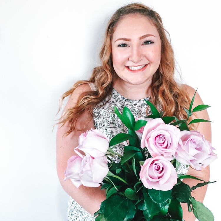Sarah, Well-Grown Home founder, smiling and holding light pink roses